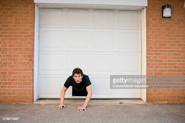 Young man crawling through hole in garage door