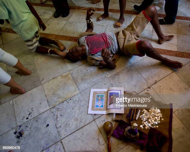 A young man crawls on the floor to fulfill a promise to San Lazaro on December 16 2017 in La Habana Cuba Thousands of believers gather at the Shrine...