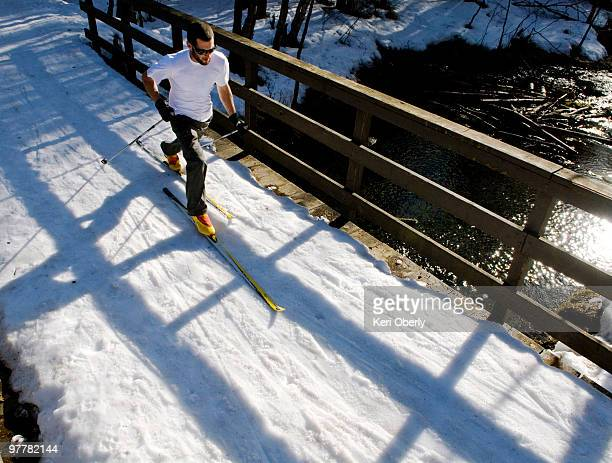 A young man cross country skis on a trail over a bridge in Anchorage, Alaska.