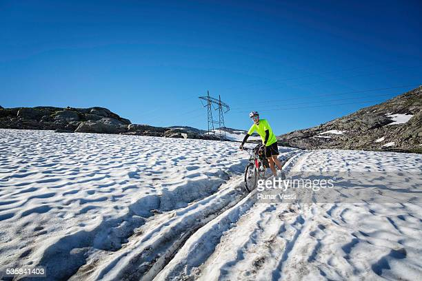 Young man crosses snow with a bike at Rallarvegen