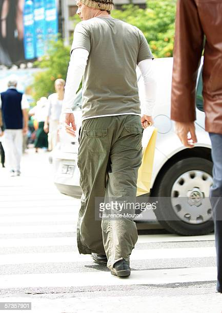 young man crossing street - cargo pants stock photos and pictures