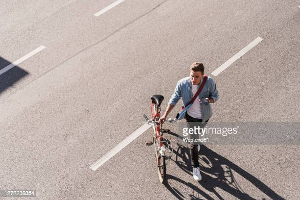young man crossing street with bicycle in city - leben in der stadt stock-fotos und bilder