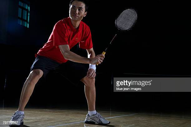 Young man crouches and holds his racket as if preparing to return a shot during a game of badminton.