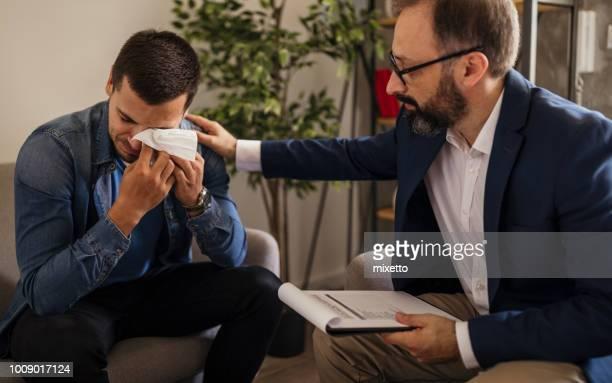 joven llorando durante la psicoterapia - hombre llorando fotografías e imágenes de stock