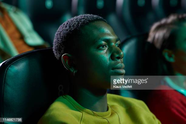 young man crying while watching movie in cinema hall - color out of space 2019 film stockfoto's en -beelden