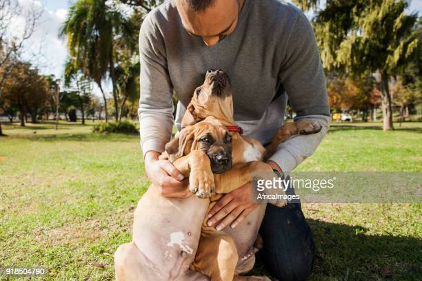 Young man cuddling his puppies while playing at the park.