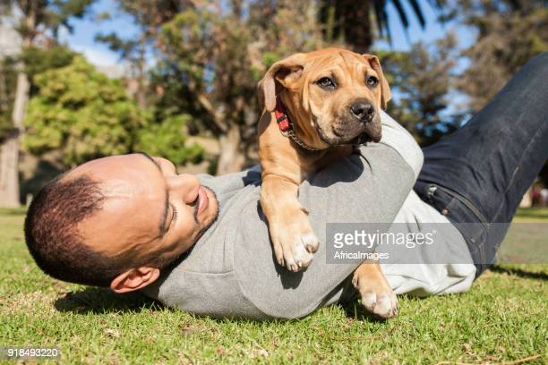 Young man cuddling his puppy on the grass at the park.