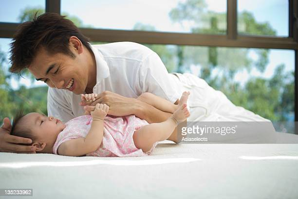 Young man cuddling with his daughter on the bed and smiling