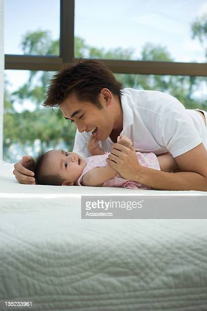 Young man cuddling with his daughter on the bed