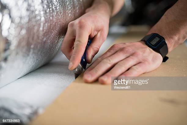 Young man cutting a insulating material for a laminate-flooring