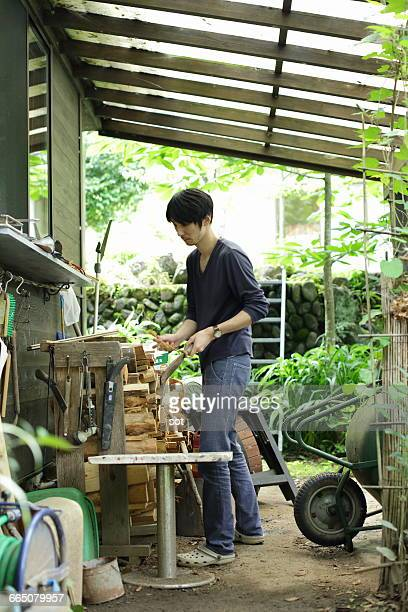 Young man cutting firewood near house
