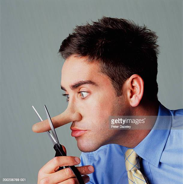 young man cutting nose with scissors, side view, close-up - big nose stock photos and pictures
