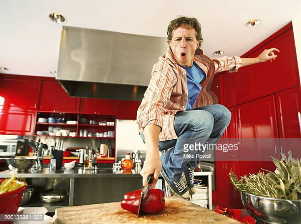 Young man cutting red bell pepper in kitchen, jumping in air
