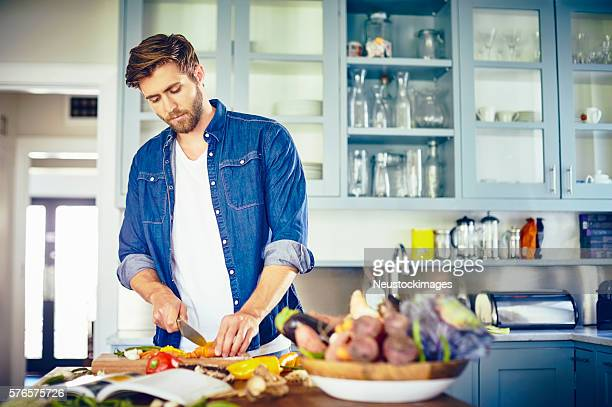 Young man cutting vegetables at kitchen island