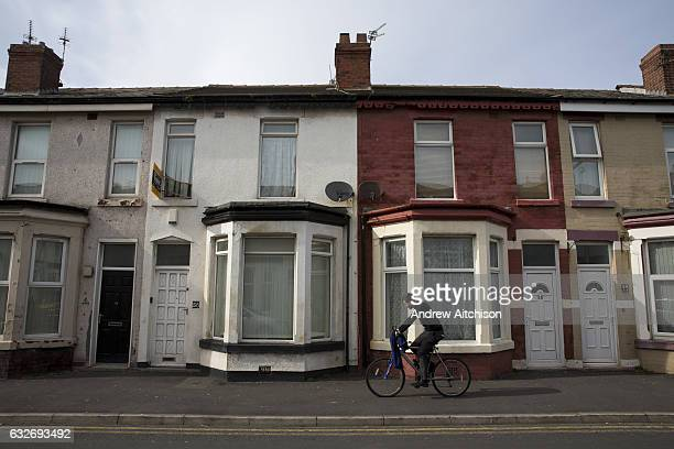 Young man cycles past a row of terraced houses in Bloomfield ward, Blackpool, Lancashire, England, United Kingdom. Bloomfield ward is the poorest...