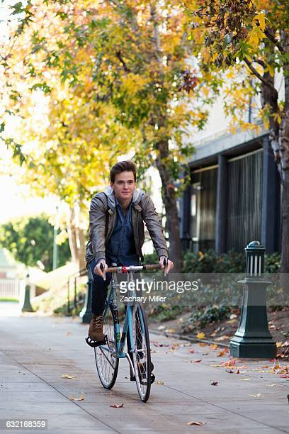 young man cycling along sidewalk - monrovia california stock pictures, royalty-free photos & images