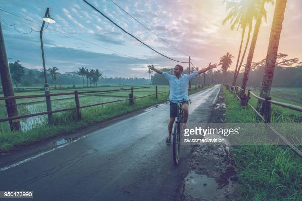 young man cycling at sunrise by the rice fields, indonesia - arms outstretched stock pictures, royalty-free photos & images