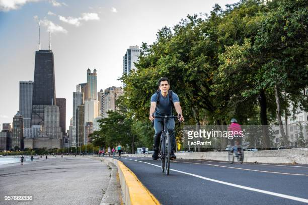 young man cycling in chicago by michigan lake, commuting to work - chicago illinois stock pictures, royalty-free photos & images
