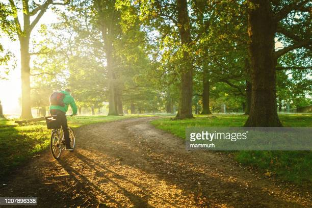 young man cycling in richmond park, london - environmental conservation stock pictures, royalty-free photos & images