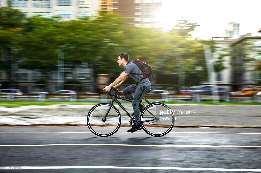 Young man cycling in the city, commuting to work : Stock Photo
