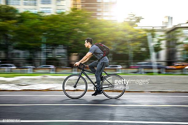 young man cycling in the city, commuting to work - riding stock pictures, royalty-free photos & images