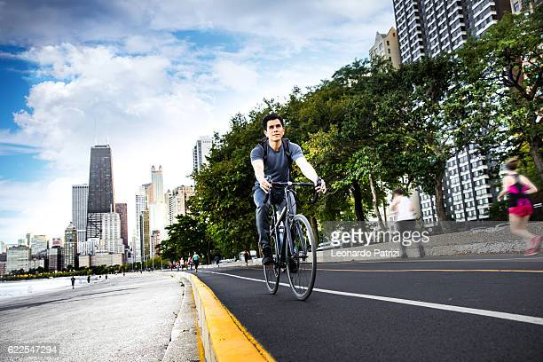 young man cycling in the city, commuting to work - cook county illinois stock photos and pictures