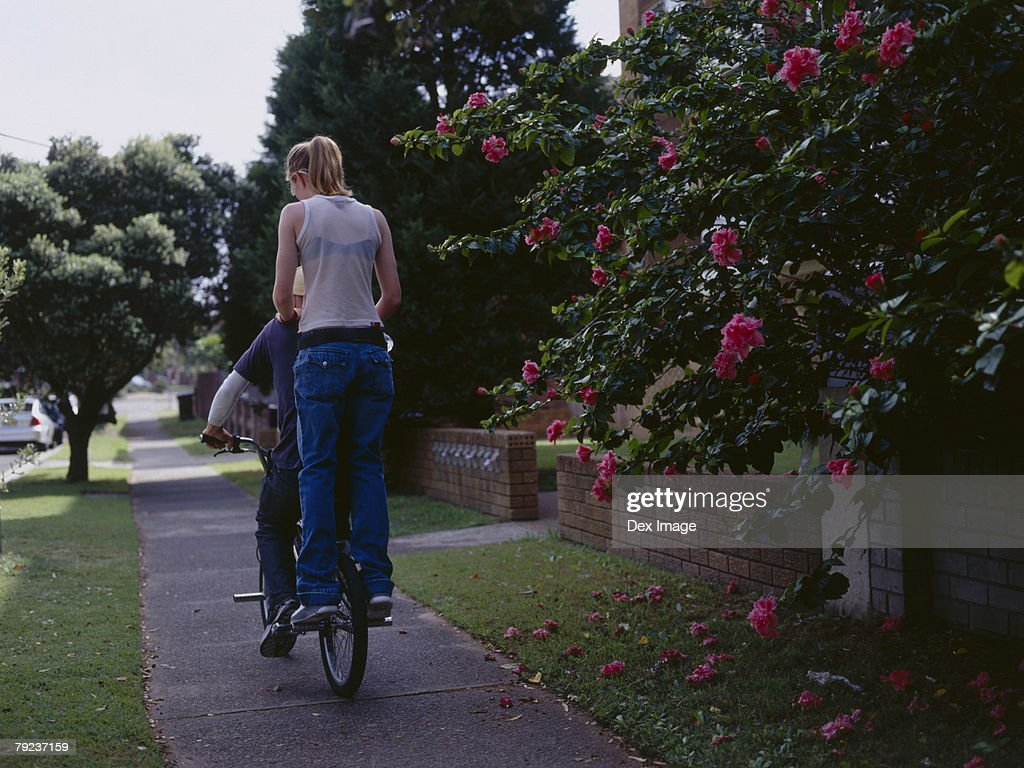 Young man cycling with young woman on back of bike, rear view : Stock Photo
