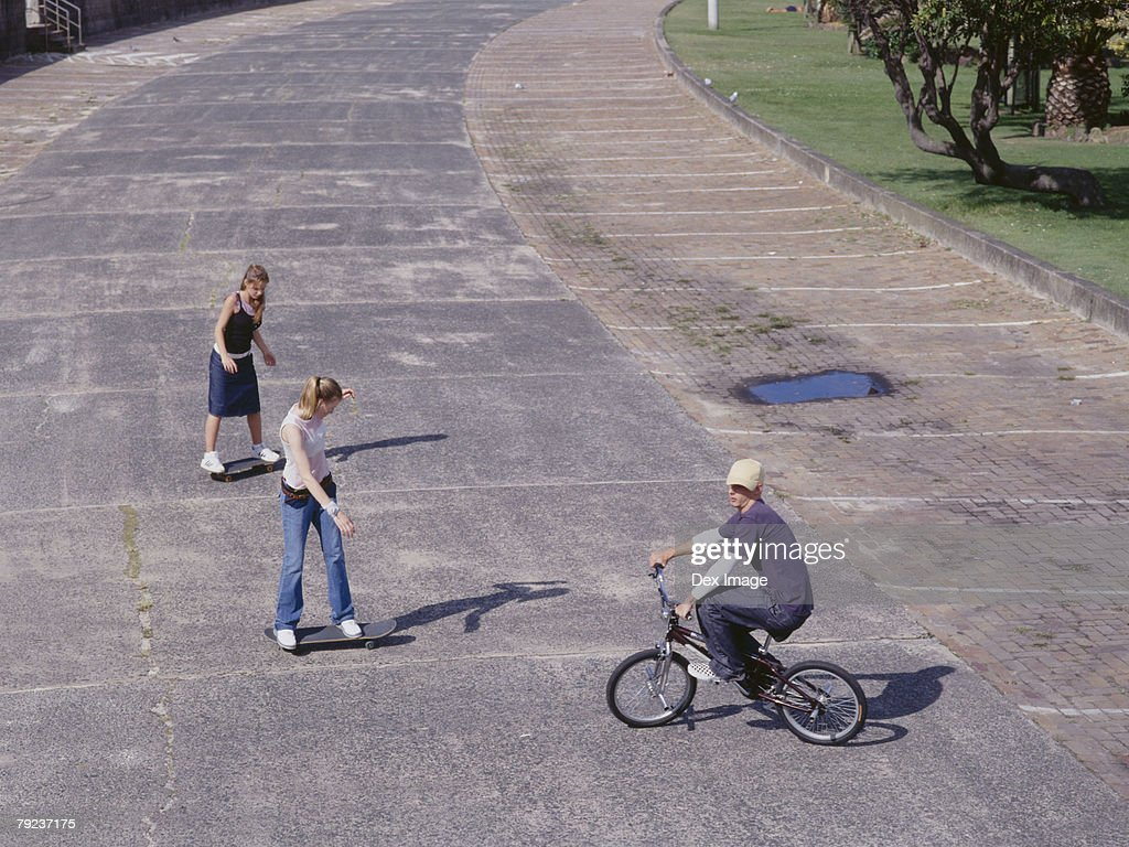 Young man cycling, young women skateboarding : Stock Photo