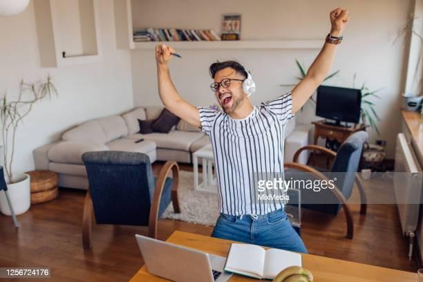 自宅で仕事の後に踊り、歌う若者 - 仕事後 ストックフォトと画像