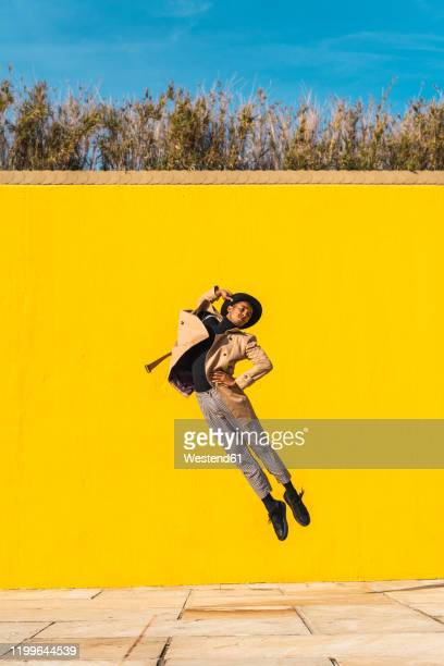young man dancing in front of yellow wall, jumping mid air - fashion show - fotografias e filmes do acervo