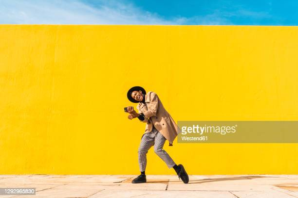 young man dancing in front of yellow wall, taking selfies - dancer stock pictures, royalty-free photos & images