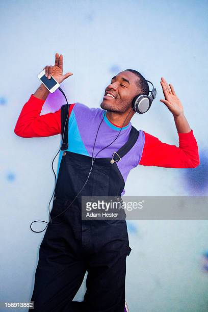 A young man dancing outside with headphones.