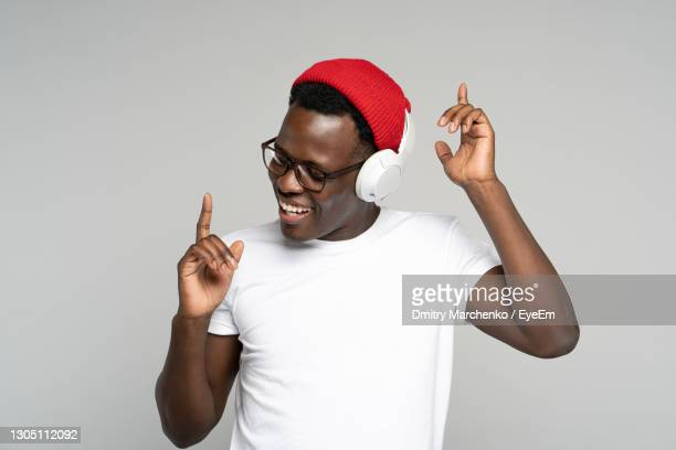 young man dancing while listening music against white background - headphones stock pictures, royalty-free photos & images