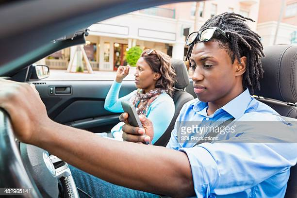 Young man dangerously looking down at cell phone while driving