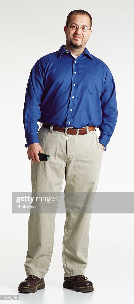 young man dark hair glasses goatee wears blue oxford shirt tan pants looks to camera phone in hand : Foto de stock