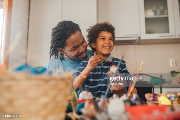 young man decorating easter eggs with his son - african american easter stock photos and pictures