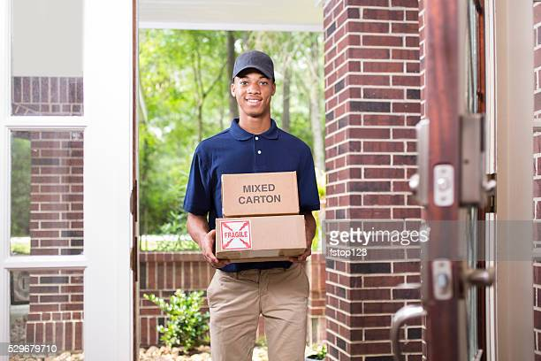 Young man delivers packages to customer at home.