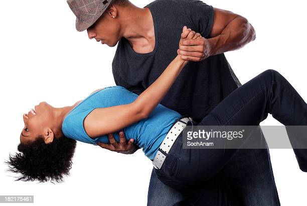 A young man dips a woman while dancing closely together