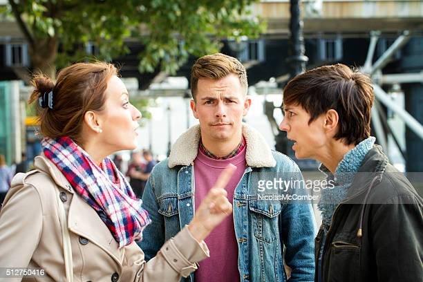Young man dismayed as his girlfriend argues with ex