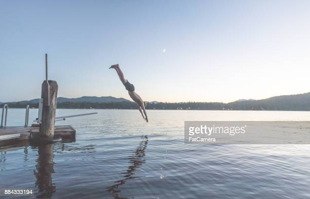 Young man dives into a lake off pier at dusk