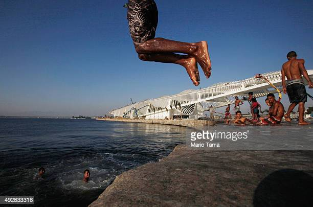 A young man dives into the polluted Guanabara Bay as people from the nearby Providencia 'favela' community gather in front of the Museum of Tomorrow...