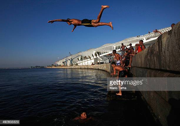 A young man dives into the polluted Guanabara Bay as residents from the nearby Providencia 'favela' community gather in front of the Museum of...