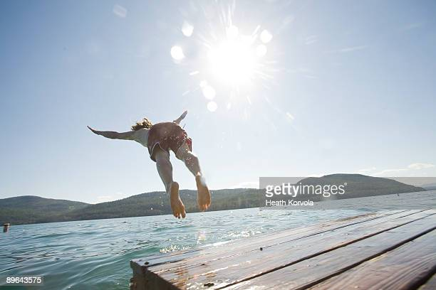 A young man dives off of a dock.