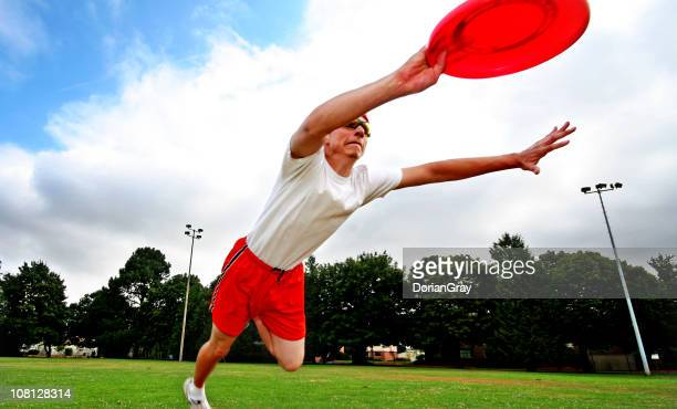 Young Man Diving and Catching Frisbee in Field