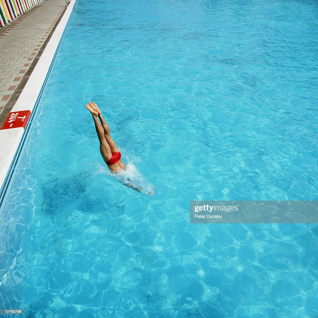 Young man diving head first into swimming pool : Stock Photo
