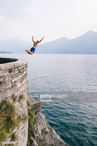 Young man diving in the water from a cliff.