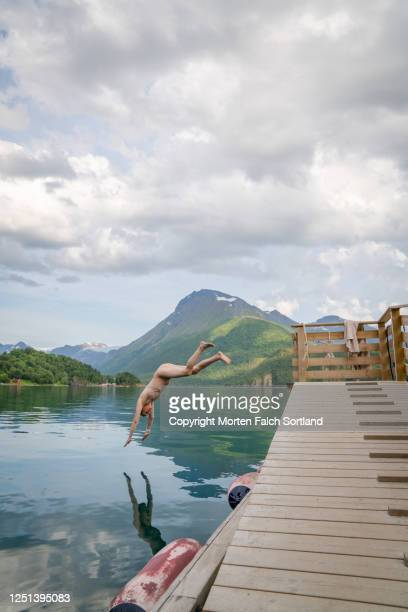 young man diving into a lake in halsa, norway - skinny dipping stock pictures, royalty-free photos & images