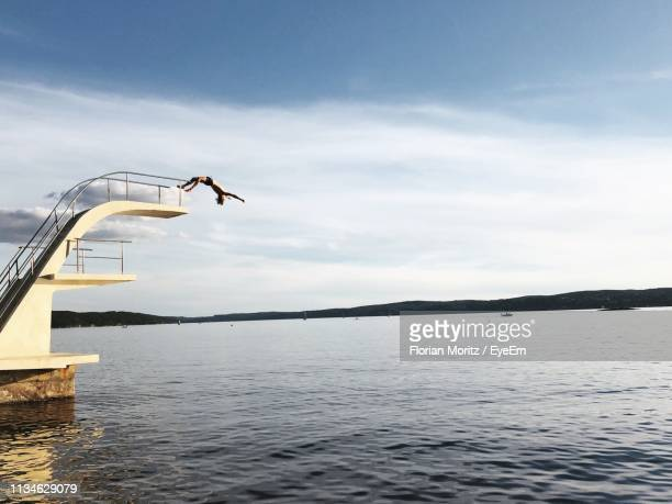 young man diving into lake against sky - diving platform stock pictures, royalty-free photos & images