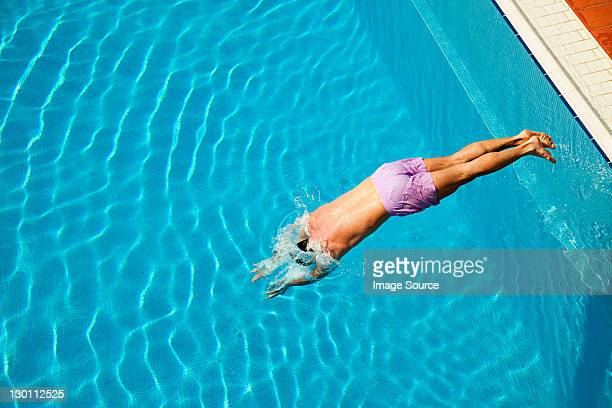 young man diving into swimming pool - diving into water stock pictures, royalty-free photos & images