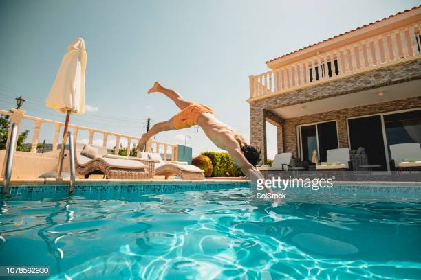 young man diving into the swimming pool - cyprus island stock pictures, royalty-free photos & images